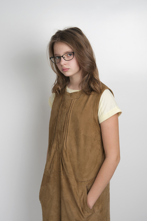 age 10: Cute little girl in stylish suede dress. Studio photography on a light gray background. Age of child 10 years.