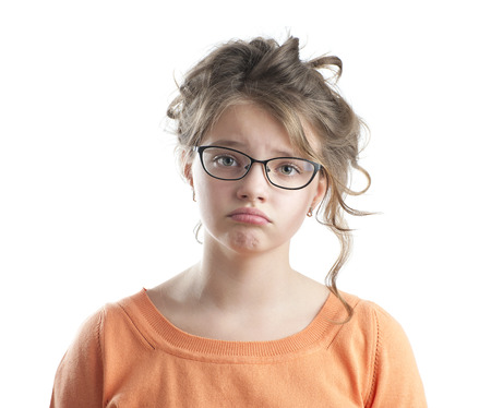 Portrait of a sad little girl. Studio photography on a white background. Age of child 10 years.