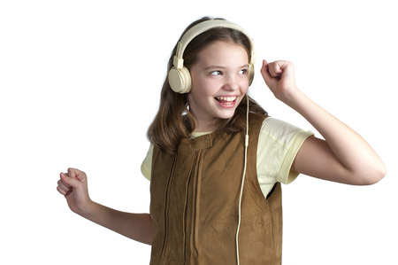 age 10: Dancing girl with music headphones on her head. Studio photography on a white background. Age of child 10 years.