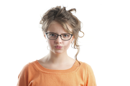 age 10: Portrait of an angry little girl. Studio photography on a white background. Age of child 10 years. Stock Photo