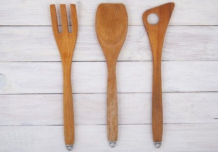 photography background: Wooden kitchen utensils on a background of white boards. Studio photography. Background - painted wooden boards.