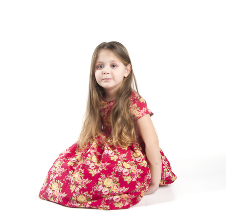 4 of a kind: Little girl with long hair in a red dress. Studio photography on a white background. Age of child 4 years.