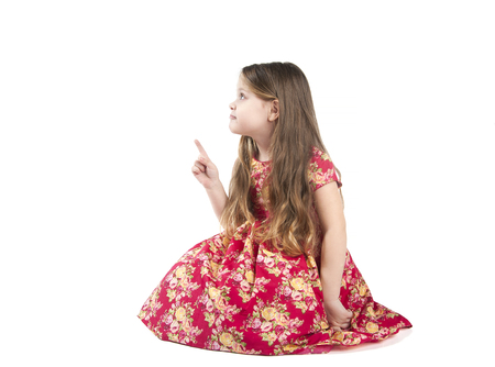 4 of a kind: The little girl shows a finger to the side. Studio photography on a white background. Age of child 4 years. Stock Photo