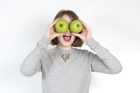horizontal haircut: Little girl with two green apples on a light gray background.