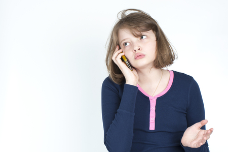 horizontal haircut: Little girl emotional talking on mobile phone on a light gray background.