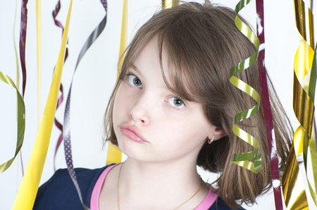 horizontal haircut: Portrait of the girl close up among the multicolored confetti on a light gray background.