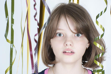 age 10: Portrait of a girl among the multicolored confetti. Studio photography on a light gray background. Age of child 10 years. Stock Photo