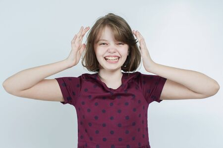 Portrait of the laughing girl who keeps her head on a light gray background. Stock Photo