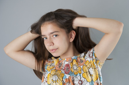 dishevel: Portrait of a young brunette woman with long hair. Studio photography on a light gray background. Stock Photo