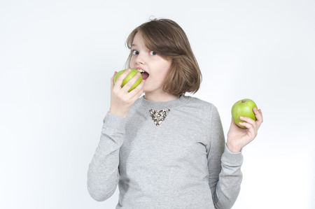 age 10: Girl with two green apples. Studio photography on a light gray background. Age of child 10 years.