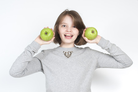 age 10: Girl holding a green apple varieties Granny Smith. Studio photography on a light gray background. Age of child 10 years. Stock Photo