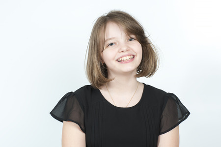 age 10: Portrait of a smiling girl in a black blouse. Studio photography on a light gray background. Age of child 10 years. Stock Photo