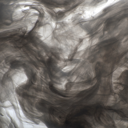 weightless: Background of black acrylic paint in water (smoke). Studio photography on a white background.