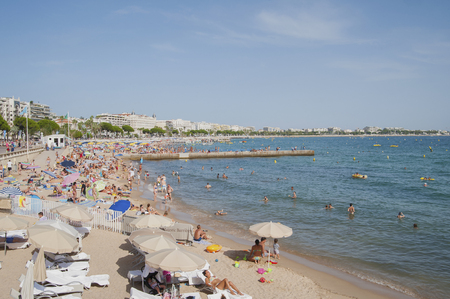 scored: FRANCE, CANNES - AUGUST 6, 2013: A lot of people on the beach of La Croisette. Editorial