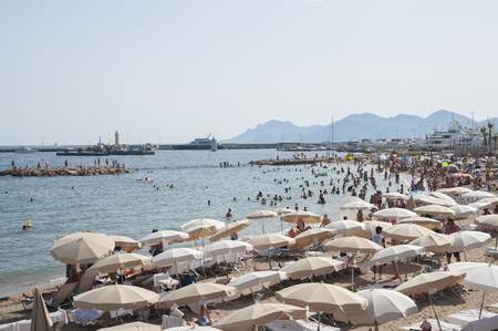 scored: FRANCE, CANNES - AUGUST 6, 2013: A lot of people on the beach near the Palais des Festivals. Editorial