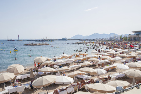 scored: FRANCE, CANNES - AUGUST 6, 2013: People relax on the beach during the high season. Editorial