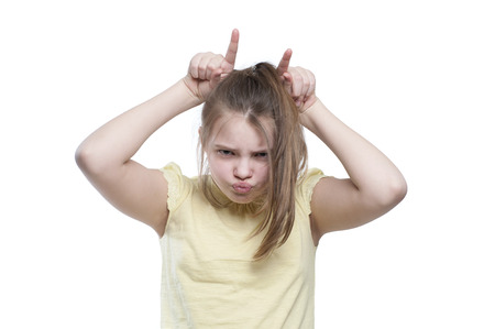 exasperated: Girl teenager shows a cow. Studio photography on a white background. Age of child 11 years. Stock Photo