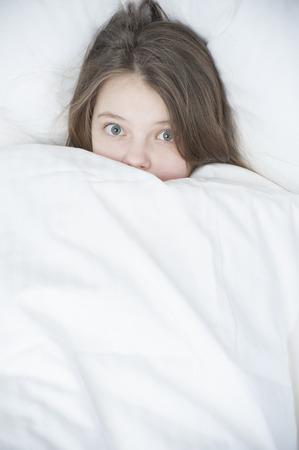 11 years: Child looks out from under the blanket. Studio photography in bright colors. Age of child 11 years.