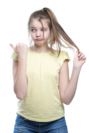 11 years: Girl holds her hair and shows finger in the direction. Studio photography on a white background. Age of child 11 years. Stock Photo