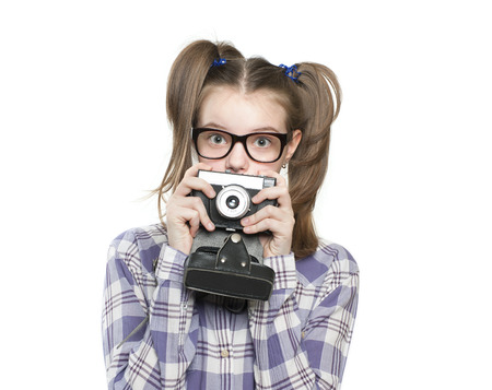 11 years: Girl teenager holding a camera. Studio photography on a white background. Age of child 11 years.