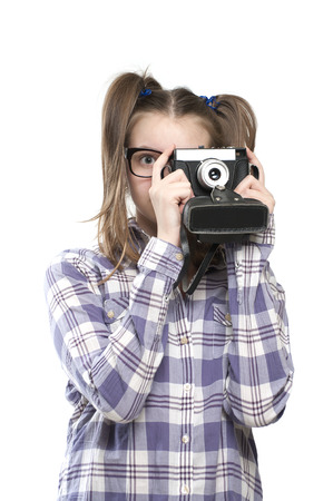 11 years: Girl teenager with a camera in hand. Studio photography on a white background. Age of child 11 years.