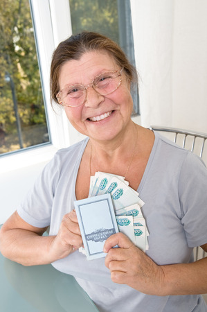 thousandth: Elderly woman with Russian money and savings book. Stock Photo