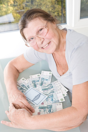 thousandth: An elderly woman with a bunch of Russian money and savings book. Stock Photo