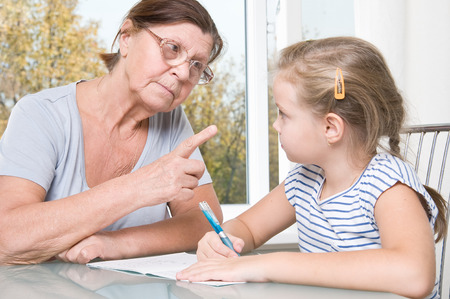 Grandmother and granddaughter doing homework. Stock Photo