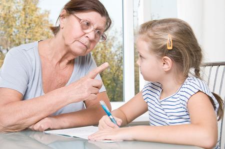 rigor: Grandmother and granddaughter doing homework. Stock Photo