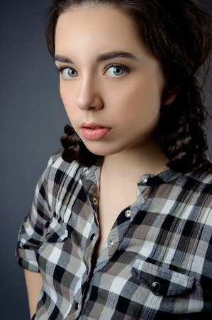 grey eyed: Beauty portrait of a beautiful brunette girl on a gray background.