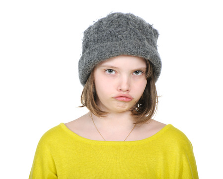 saddened: Portrait of resentful teenager in funny hat knitted jumper and bright.  Stock Photo