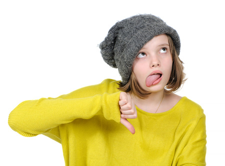 Portrait of unhappy teenage girl showing gesture thumbs down.
