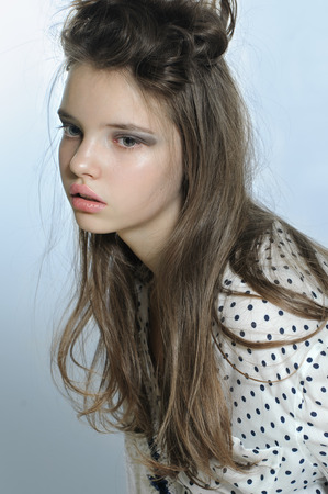 Portrait of teen girl in a stylish shirt and casual hairdo. Fashion photography in a soft tone. Stock Photo