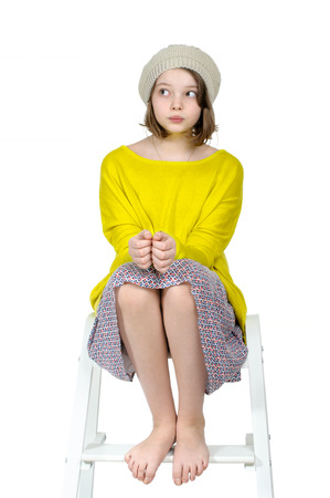 Barefoot girl sitting on a stepladder with a mysterious look. Stock Photo