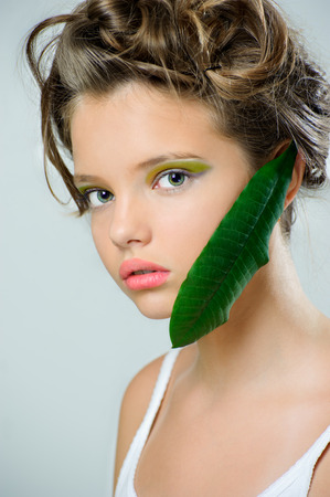 rigorous: Beauty portrait of a young girl with bright green makeup and a fresh leaf on her face.  Stock Photo
