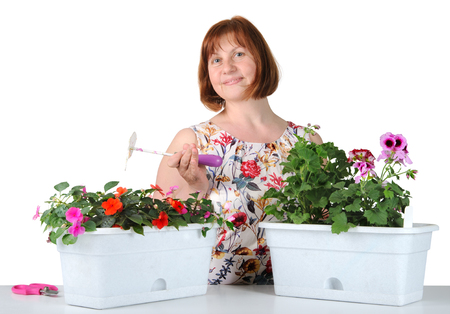 Portrait of pretty middle-aged woman with Pelargonium and Impatiens.