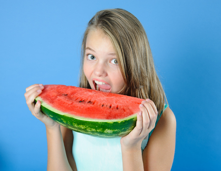 Cute teen girl takes a bite of watermelon. Studio photography on a light blue background.