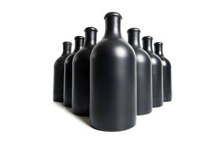 Matzwarte flessen op een witte achtergrond close-up.