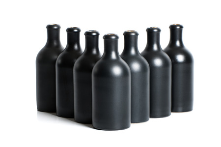 Set van matte zwarte klei flessen op een witte achtergrond. Stockfoto