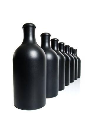 Zeven mat zwarte flessen op een witte achtergrond. Stockfoto