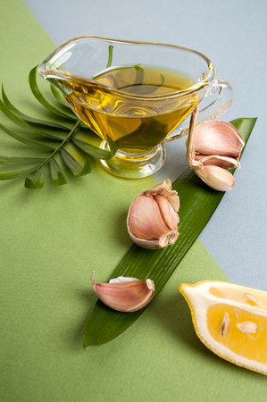 Fresh garlic, lemon slices and olive oil on a blue-green textured background.  Stock Photo