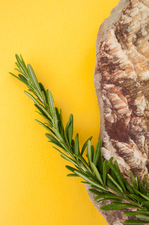 A branch of fresh rosemary and natural sea stone on a bright yellow background.