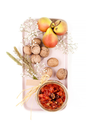 Pear jam, pears and walnuts are served on a light pink tray on a white background top view.