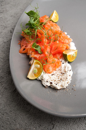 Lightly salted salmon with cottage cheese cream and limequat is served on a gray plate.