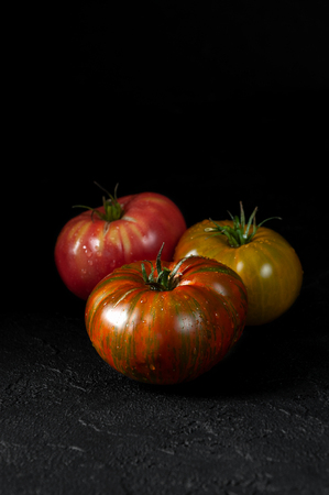 Hereditary tomatoes. Three tomatoes of different colors on a black textured background close-up.