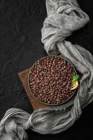 Freshly roasted coffee beans on a dark table. Low key photography flat-lay.