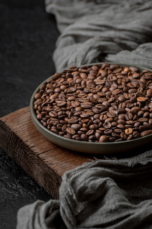 Roasted coffee beans in a plate on a wooden stand. 写真素材