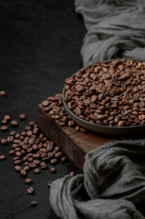Roasted coffee beans in a plate on a wooden stand. Photo with free space for text.
