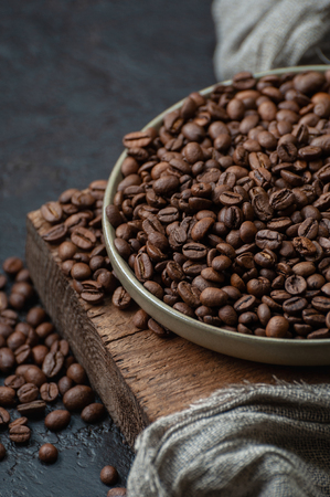 Coffee beans in a plate on a wooden stand. Close-up photography with low key. 写真素材