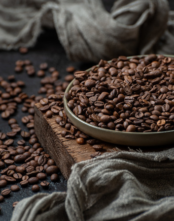 Freshly roasted coffee beans on a dark table in vintage style. Low key photography. 写真素材